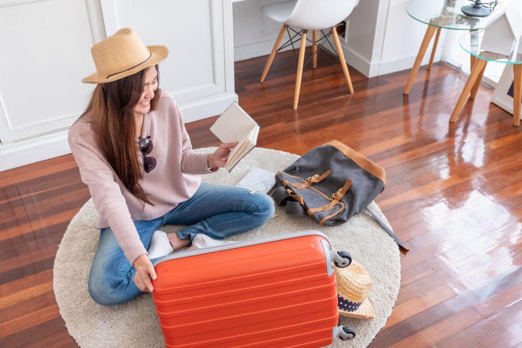 Mulher asiática checa a sua lista de viagem enquanto prepara a sua bagagem para viajar em família.